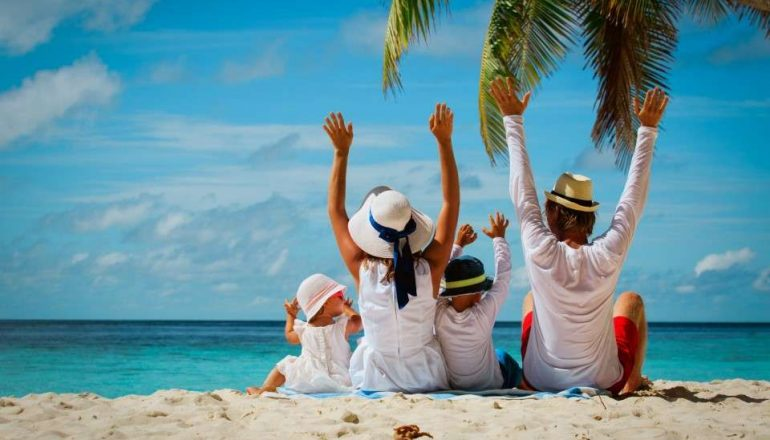 happy-family-with-two-kids-hands-up-on-beach-picture-id677652068