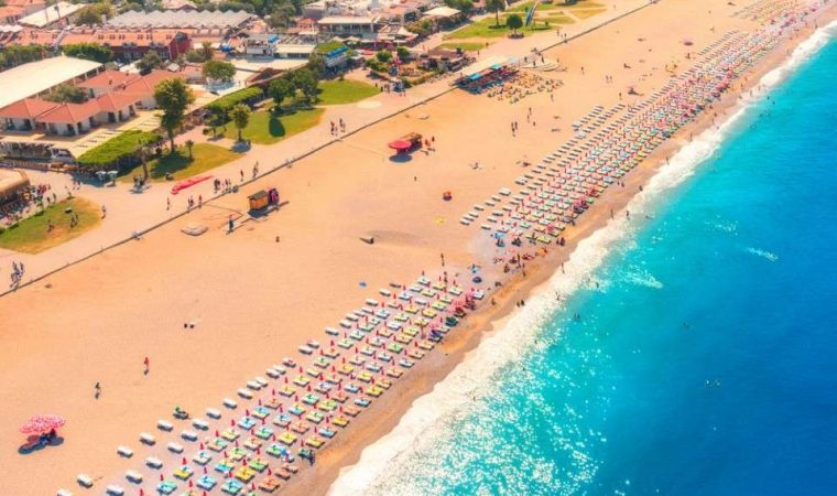 Aerial view of sandy beach with colorful chaise-lounges and blue sea in sunny bright day in Oludeniz, Turkey. Top view. Seascape with seashore, azure water and waves. Holiday. Travel and resort.Nature
